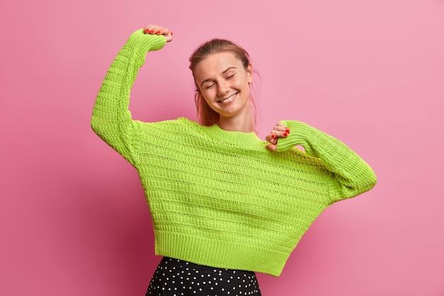 のんきなエネルギーを与えられた若い女性は、楽観的で嬉しく感じ、手を上げて満足し、目を閉じて、ニットの緑のセーターを着て、完璧な休日を楽しんでいます
