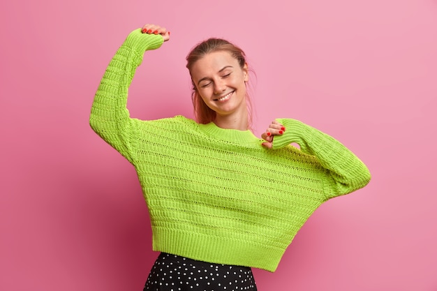 Carefree energized young woman feels optimistic and glad, raises hands and feels pleased, keeps eyes closed, dressed in knitted green sweater, enjoys perfect day off