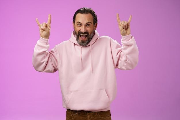 평온한 열정적 인 흥분된 성숙한 수염 난 남자 회색 머리 재미 쇼 락 앤 롤 제스처에 참석하는 멋진 헤비 메탈 콘서트 찡그린 찾고 행복하고 낙관적 인, 보라색 배경.