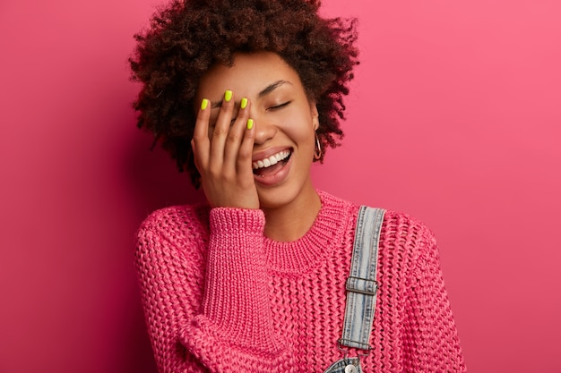 Carefree ethnic girl cannot stop laughing, keeps hand on face, has cheerful face, smiles positively, has good sense of humor, expresses happiness, wears knitted jumper, poses over pink wall