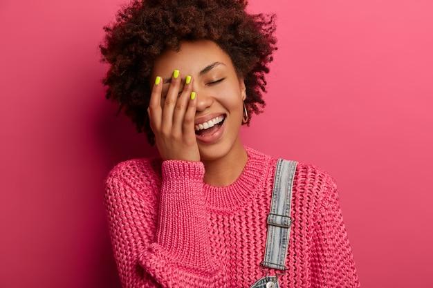 のんきな民族の女の子は笑いを止めることはできません、顔に手を保ち、陽気な顔をして、前向きに笑って、ユーモアのセンスがあり、幸せを表現し、ニットのジャンパーを着て、ピンクの壁にポーズをとる