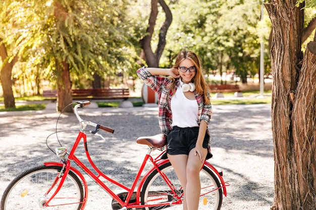 人生を楽しんでいる赤い自転車でのんきな金髪の女性。春の公園で余暇を過ごす白人のブロンドの女の子。