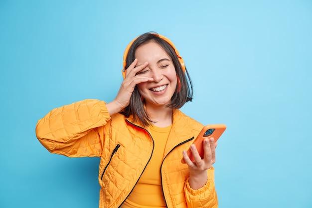 Spensierata donna asiatica alla moda sorride positivamente tiene gli occhi chiusi mano sul viso si diverte ascolta musica tiene smartphone moderno indossa cuffie wireless esprime emozioni positive pose indoor