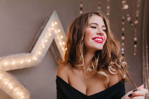 Carefree fashionable woman playing with shiny curly hair on dark wall. relaxed young lady with romantic hairstyle laughing  during holiday photoshoot.