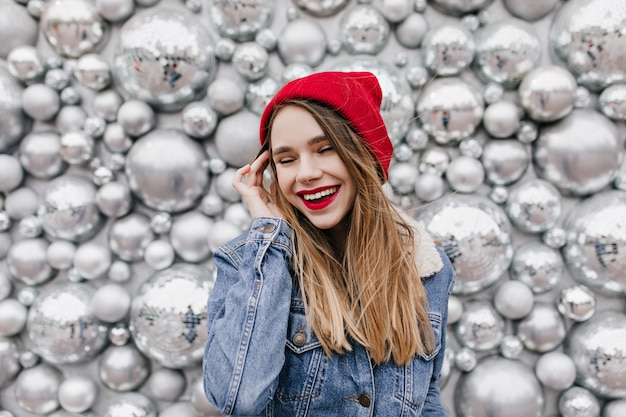 光沢のある壁にかわいい笑顔でポーズをとる明るいメイクののんきな女性モデル。ディスコボールの近くで笑っている赤い帽子とデニムジャケットの魅力的な白人女性。