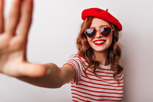 Modello femminile francese spensierato in berretto sorridente ragazza emotiva in accessori casual in posa.