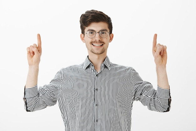 Carefree friendly european male student with moustache and beard in trendy round glasses and striped shirt, raising index fingers and pointing up while smiling broadly, telling he found great place