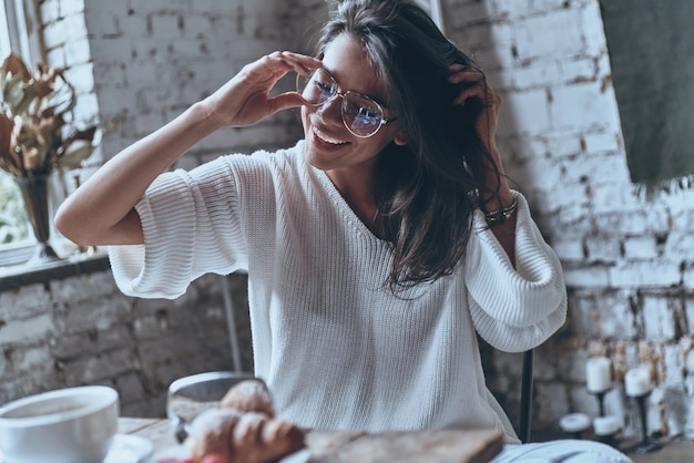 Carefree fun. attractive young woman adjusting her eyewear while sitting at the table at home