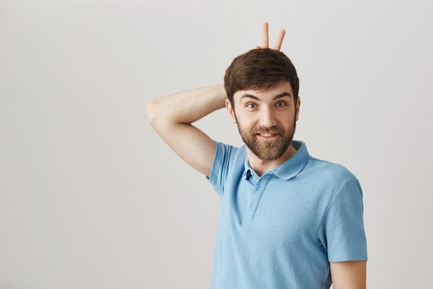 Spensierato divertente e carino giovane uomo barbuto in posa
