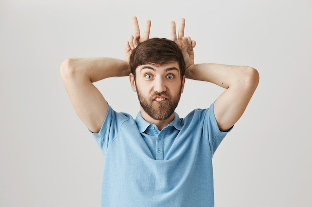 Carefree funny young bearded man posing