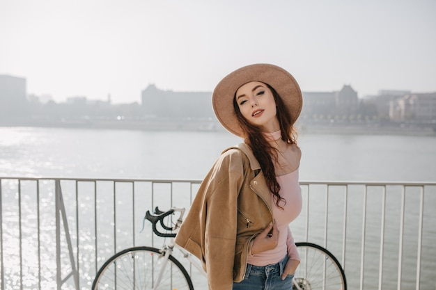Беззаботная рыжая женщина в бежевой куртке позирует возле велосипеда