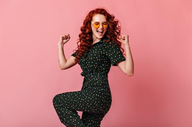Беззаботная женщина имбиря показывая жест да. счастливая девушка в солнечных очках, танцы на розовом фоне.