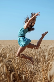 Carefree girl in a blue sundress enjoys the sun in a wheat field