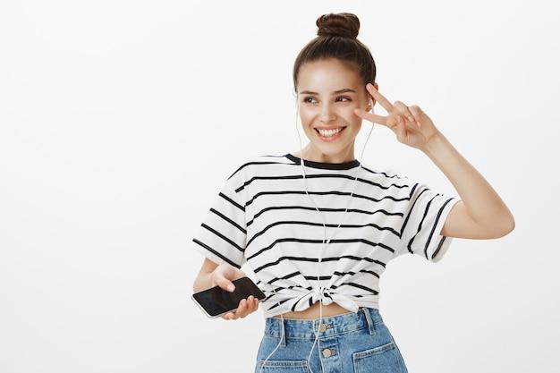 춤추는 이어폰에 평온한 소녀, 스트리밍 모바일 앱에서 음악 듣기