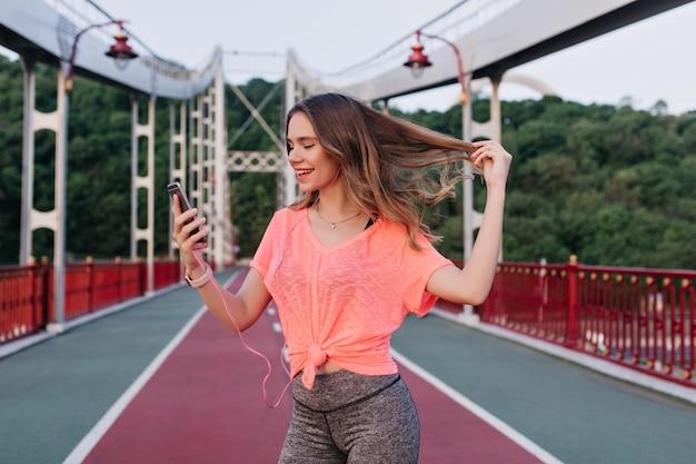 Беззаботная девушка играет со своими волосами, фотографируя себя на стадионе. удивительная кавказская женщина, делающая селфи со смартфоном.