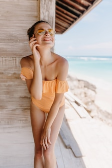 Carefree girl posing at beach with eyes closed and sincere smile. outdoor shot of magnificent slim lady in orange swimsuit.