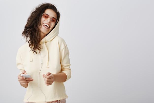 Carefree girl singing karaoke app in earphones, holding mobile phone
