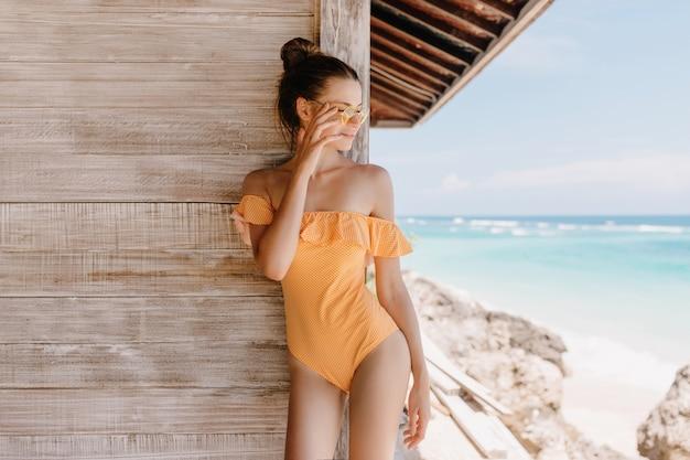 Ragazza spensierata in costume da bagno vintage in piedi vicino a casa in legno e guardando il mare. foto all'aperto di splendida donna bruna con acconciatura alla moda rilassante al resort.