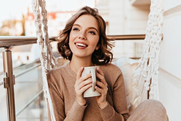 バルコニーでお茶を飲む茶色の化粧でのんきな女の子。コーヒーを楽しんでいるニットドレスの快適なブルネットの女性の写真。