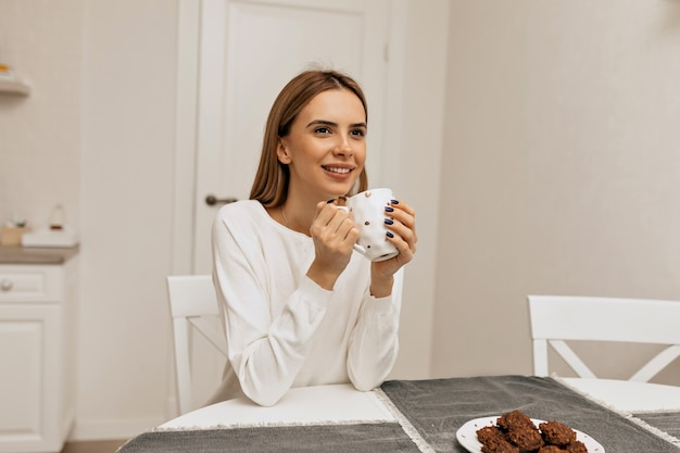 Carefree girl with drinking coffee at kitchen. photo of pleasant smiling woman in white shirt enjoying coffee break.