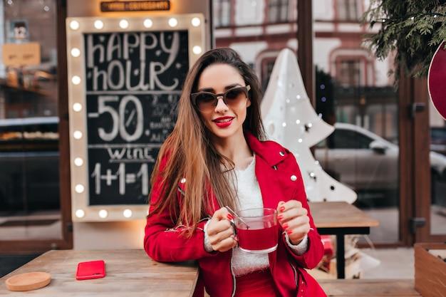 Ragazza spensierata con acconciatura lunga che beve il tè in street cafe