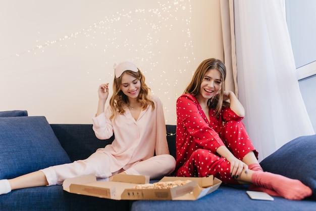 함께 피자를 먹는 귀여운 잠옷에 평온한 소녀. 빨간 파자마 여동생과 함께 소파에 앉아 패스트 푸드를 즐기는 로맨틱 한 젊은 여자.