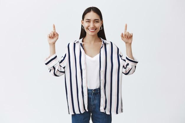 Беззаботная симпатичная европейка в полосатой блузке и джинсах, радостно улыбаясь, поднимая руки и указывая вверх