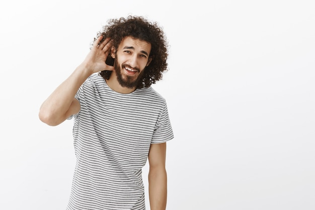 Carefree good-looking guy with beard and afro hairstyle, holding hand near ear and asking question