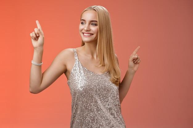 Беззаботная красивая стильная гламурная белокурая молодая женщина 20-х годов в серебряном блестящем платье танцует с удовольствием, развлекается на выпускном вечере вечеринки, встряхивая тело, поднимая указательные пальцы, красный фон