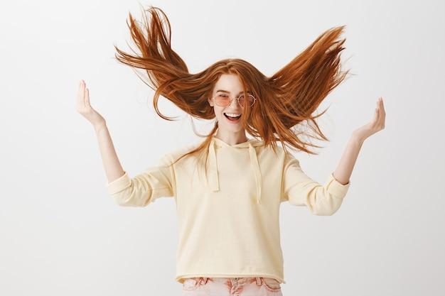 Беззаботная великолепная рыжая девушка вскидывает волосы в воздух