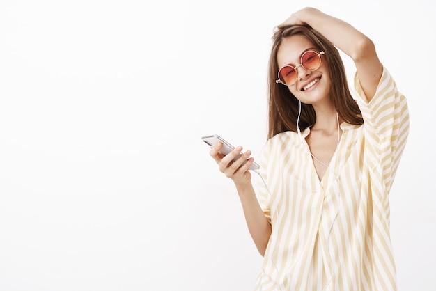 Spensierata splendida giovane donna alla moda in occhiali da sole, camicetta gialla toccando l'acconciatura inclinando la testa con gioia che tiene smartphone ascoltando musica in auricolari