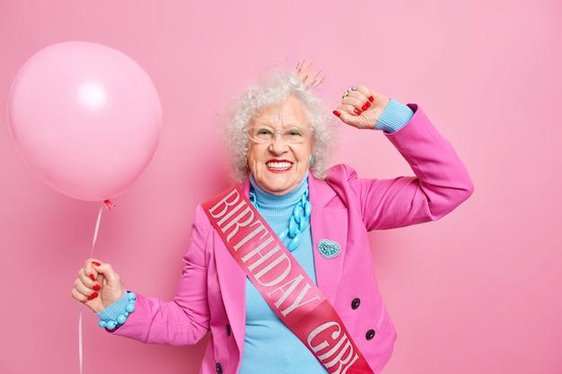 Беззаботная седая морщинистая женщина танцует беззаботные улыбки, позитивно одетая в праздничную одежду, носит ленту на день рождения, держит надутый воздушный шар