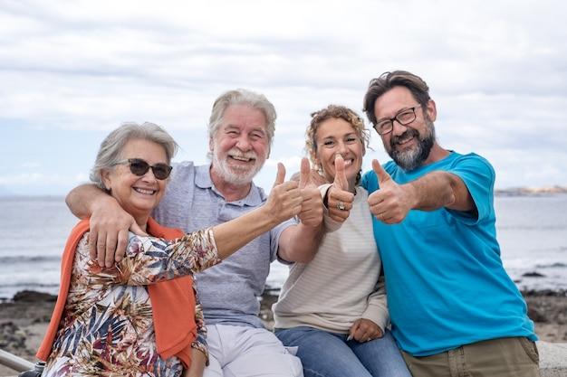 Беззаботная группа семьи из разных поколений, глядя на камеру с большими пальцами руки, сидя на открытом воздухе у моря. горизонт над водой и облачным небом