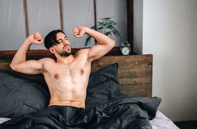 Беззаботный парень наслаждается новым днем. сексуальный, счастливый бородатый мужчина в постели