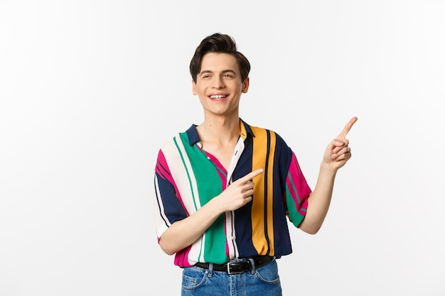 スタイリッシュなシャツを着たのんきな男が右上隅に指を指して、プロモーションバナーやロゴを表示し、笑顔で誰かと話し、白の上に立っています