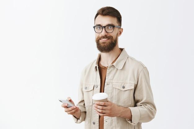 Uomo barbuto bello spensierato in vetri che posano contro il muro bianco