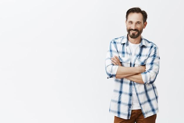 Беззаботный красивый бородатый зрелый мужчина смеется и улыбается