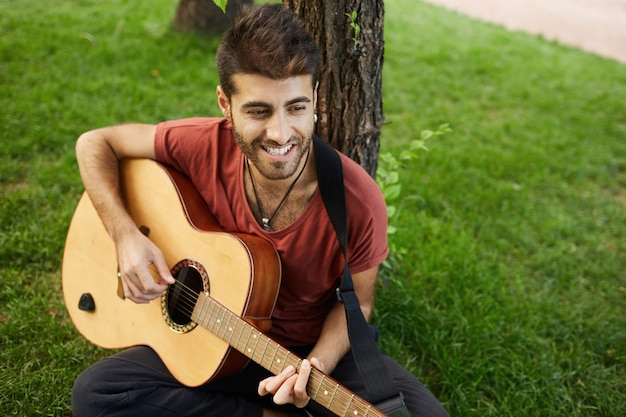 Carefree handsome guy playing guitar in park