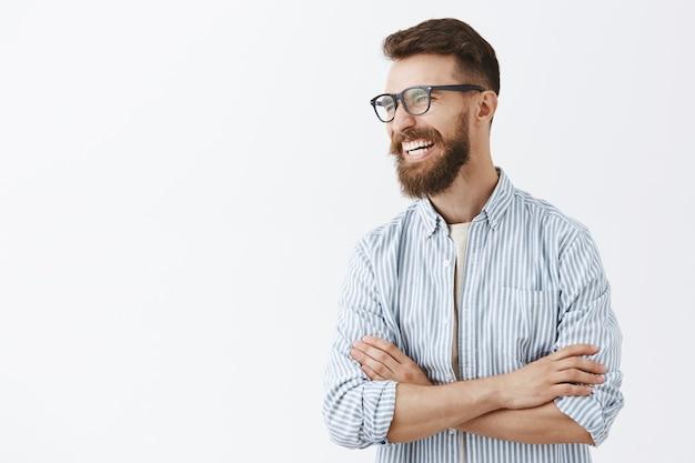 Беззаботный красивый смеющийся мужчина в очках улыбается счастливым
