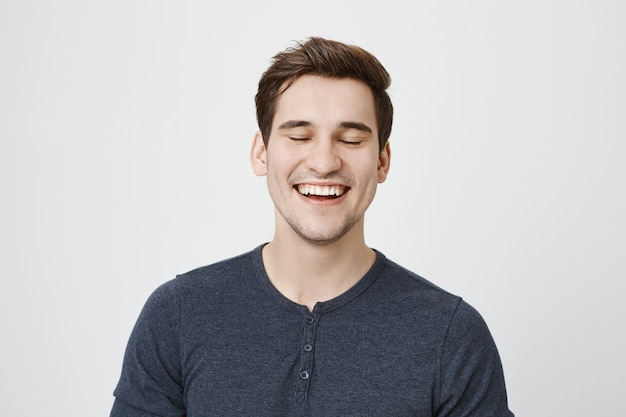 屈託のないハンサムな男が笑って、幸せそうに見えて
