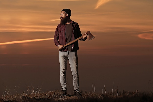 Carefree happiness freedom concept hipster man with beard with axe in hand and moustache in hat jumps with axe on mountain top on cloudy sky