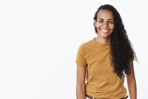 のんきな幸せなアフリカ系アメリカ人女性が白い背景の上に広く笑っている