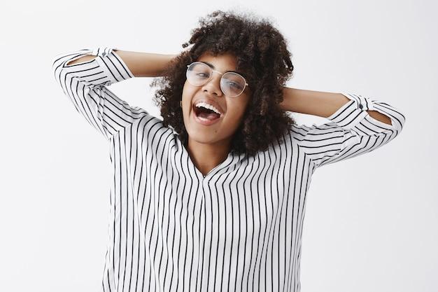 頭の後ろで手をつないでアフロの髪型と笑顔と喜びとリラックスしたリードの高揚したライフスタイルを笑顔でのんきな幸せとうれしそうな黒肌の女性