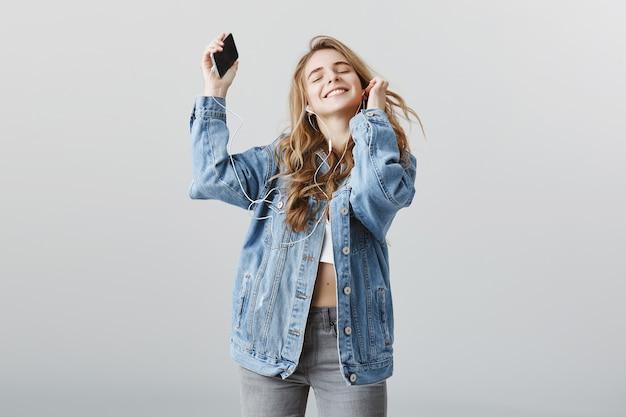 Беззаботная счастливая блондинка танцует под музыку в наушниках, радостно улыбаясь