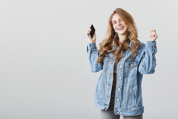 ヘッドフォンで音楽に合わせて踊るのんきな幸せなブロンドの女の子、うれしそうな笑顔