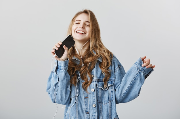 Carefree happy blond girl playing karaoke app on mobile phone, singing into smartphone in earphones