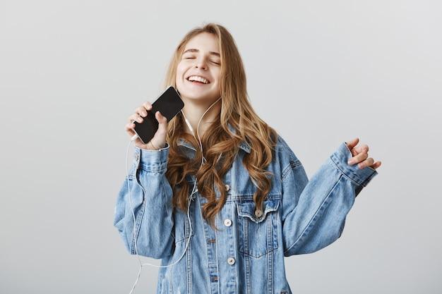 Беззаботная счастливая белокурая девушка играет в караоке-приложении на мобильном телефоне, поет в смартфон в наушниках