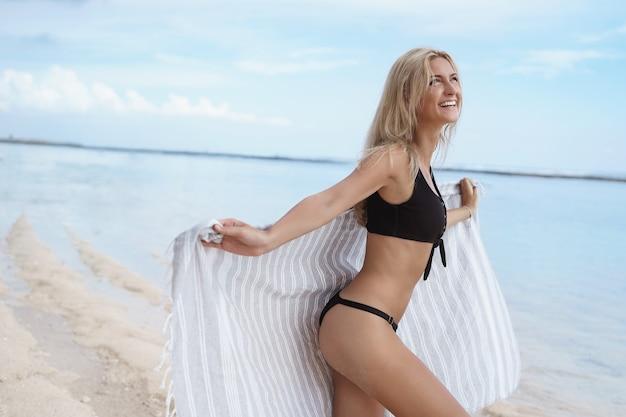 Carefree happy blond woman dancing wearing bikini holds beach towel look up to the ski.