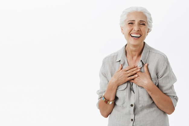 웃고 웃고 회색 머리를 가진 평온한 행복 노인 여성