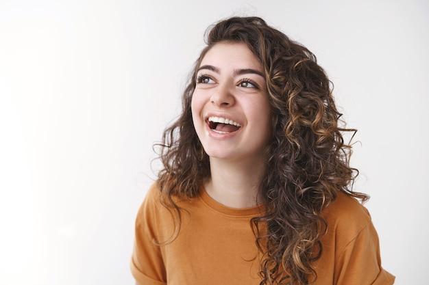 근심 없는 행복한 재미있는 매력적인 곱슬머리 여자친구가 크게 웃으면서 왼쪽 상단 모서리를 웃으면서 즐겁게 웃으면서 재미있는 농담 코미디 순간을 웃고, 흰색 배경에 서 있습니다.